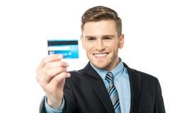 Geschäftsmann, der seine Geldautomatenkarte anzeigt Lizenzfreie Stockfotos
