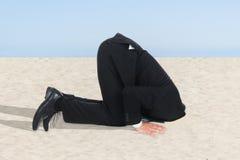 Geschäftsmann, der seinen Kopf im Sand versteckt Stockfotos