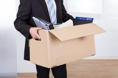 Geschäftsmann, der sich heraus mit Pappschachtel bewegt Lizenzfreie Stockfotos