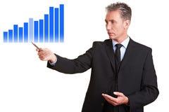 Geschäftsmann, der Statistiken zeigt Stockfotos