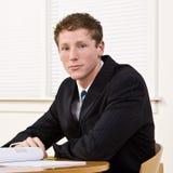 Geschäftsmann, der am Tisch sitzt Lizenzfreies Stockfoto