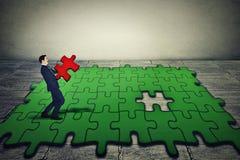 Geschäftsmann, der tragendes letztes Stück des grünen Puzzlespiels hält Stockfoto