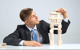 Geschäftsmann, der Turm macht Stockfoto