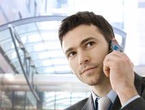 Geschäftsmann, der um Telefon ersucht Stockbild