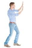 Geschäftsmann, der unsichtbare Wand gegen weißen Hintergrund drückt Lizenzfreie Stockfotografie
