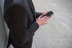 Geschäftsmann, der von der Arbeit stillsteht und beim Senden von den Mitteilungen und Unterhaltung mit seinem Smartphone Stockfoto