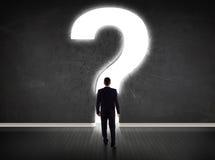 Geschäftsmann, der Wand mit einem hellen Fragezeichen betrachtet Lizenzfreie Stockbilder