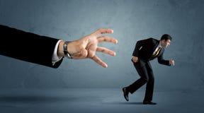 Geschäftsmann, der weg von einem Konzept der riesigen Hand läuft Lizenzfreie Stockfotos