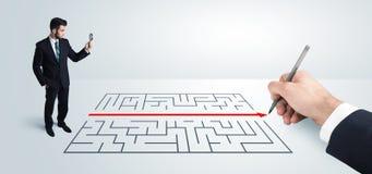 Geschäftsmann, der Zeichnungslösung zur Hand nach Labyrinth sucht Lizenzfreies Stockfoto