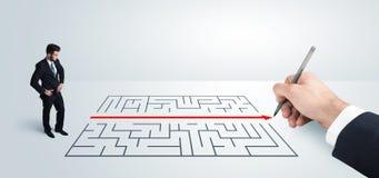 Geschäftsmann, der Zeichnungslösung zur Hand nach Labyrinth sucht Stockfotos