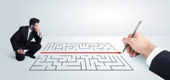 Geschäftsmann, der Zeichnungslösung zur Hand nach Labyrinth sucht Stockfoto