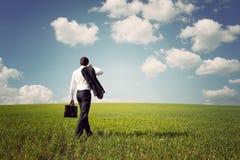 Geschäftsmann in einer Klage gehend auf ein geräumiges grünes Feld Stockfoto