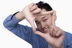 Geschäftsmann Framing His Face Stockfotografie