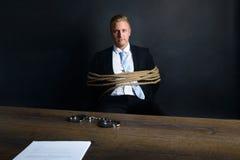 Geschäftsmann gebunden mit dem Seil, das vor Tabelle sitzt Lizenzfreies Stockfoto