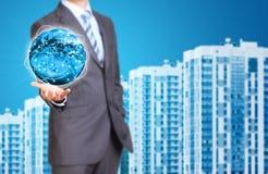 Geschäftsmann-Griff Erde Reihe der neuen Häuser wie Stockbild