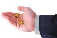 Geschäftsmann hält eine goldene Taste an Stockfotos