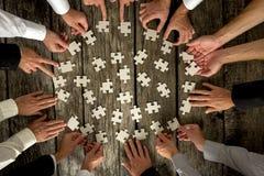 Geschäftsmann-Hände, die Puzzlespiel-Stücke auf Tabelle halten Stockfotos