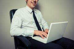 Geschäftsmann im Bürostuhl, der an Laptop arbeitet Stockbilder