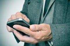 Geschäftsmann im Mantel unter Verwendung eines Smartphone Stockfotografie