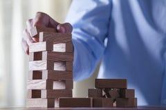 Geschäftsmann machen ein Gebäude mit hölzernen Blöcken Stockfoto
