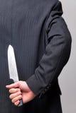 Geschäftsmann mit einem Messer hinter seinem zurück. Lizenzfreie Stockfotografie