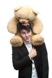 Geschäftsmann mit großem weichem Spielzeug auf Schultern Stockfoto