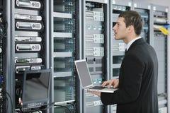 Geschäftsmann mit Laptop im Netzserverraum Lizenzfreies Stockfoto