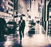 Geschäftsmann mit nasser Stadtstraße des Regenschirmes Stockfoto