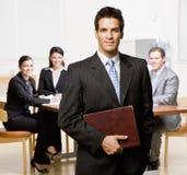 Geschäftsmann mit Notizbuch und Mitarbeitern Stockfotos