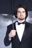 Geschäftsmann mit Regenschirm Stockfoto