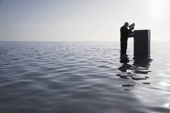 Geschäftsmann Opening Filing Cabinet im Meer Stockfoto