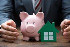 Geschäftsmann-Protecting Green Paper Haus und Piggybank Stockfotos