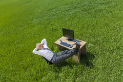Geschäftsmann-Relaxing Thinking At-Schreibtisch auf dem grünen Gebiet Lizenzfreie Stockfotos