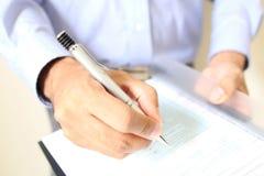 Geschäftsmann am Schreibtisch einen Vertrag unterzeichnend Lizenzfreie Stockfotografie