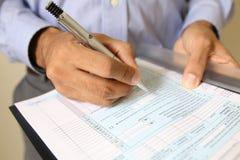 Geschäftsmann am Schreibtisch einen Vertrag unterzeichnend Lizenzfreie Stockbilder