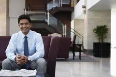 Geschäftsmann Sitting On Sofa In Hotel Lobby Stockfoto