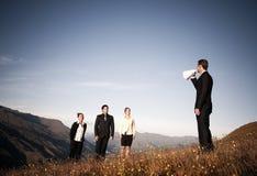 Geschäftsmann-Speaking Through Paper-Megaphon zu den Geschäftsleuten Lizenzfreies Stockfoto
