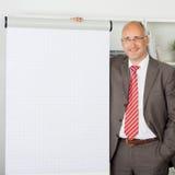Geschäftsmann Standing By Flipchart im Büro Lizenzfreies Stockbild