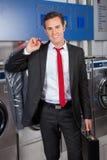 Geschäftsmann With Suitcase And Suitcover in der Wäscherei Stockfotografie