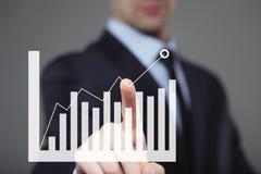 Geschäftsmann Touching ein Diagramm, das Wachstum anzeigt Stockfotos