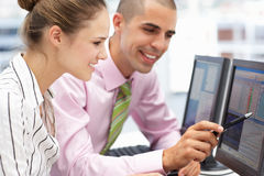 Geschäftsmann und Frau, die an Computern arbeiten Stockfotos