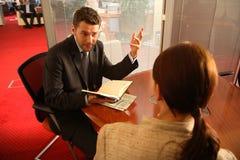 Geschäftsmann und Frau, die im Büro sprechen Stockbilder