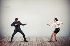 Geschäftsmann und Geschäftsfrau, die Tauziehen spielen Lizenzfreies Stockbild