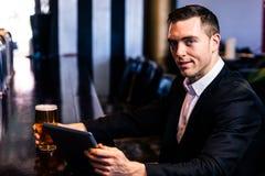 Geschäftsmann unter Verwendung der Tablette, die ein Bier isst Lizenzfreies Stockbild