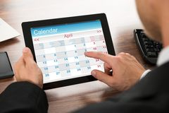 Geschäftsmann unter Verwendung des Kalenders auf digitaler Tablette Lizenzfreies Stockbild