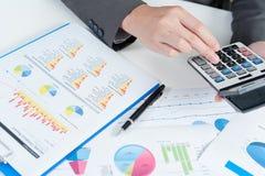 Geschäftsmann unter Verwendung des Taschenrechners analysieren Bericht Stockbild
