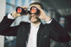 Geschäftsmann-Using Binoculars In-Büro Stockbild