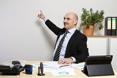 Geschäftsmann zeigt auf eine Darstellung auf der Wand. Stockbild