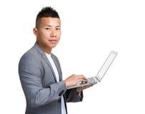 Geschäftsmannart auf tragbarem Computer Stockfotografie