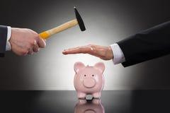 Geschäftsmanneinsparung piggybank vom Hämmern Lizenzfreie Stockbilder